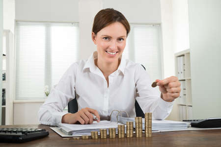 ahorros: Close-up Of Happy Businesswoman Placing Coin To Stack Of Coins