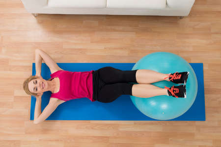 pilates ball: High Angle View Of Happy Woman Exercising With Pilates Ball On Wooden Floor
