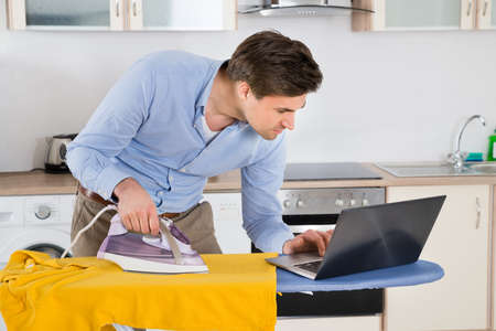 home appliances: Young Man Typing On Laptop While Ironing Cloth In Kitchen