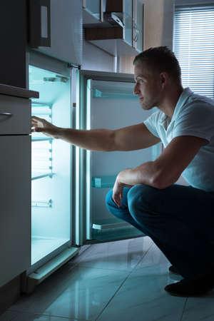 homme triste: Jeune homme assis en face de frigo vide à la nuit Banque d'images