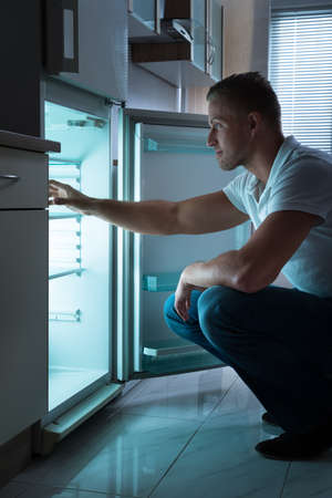 fridge: Young Man Sitting In Front Of Empty Fridge At Nighttime