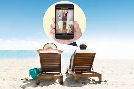 monitoreo: Hombre Con La Esposa En La Playa Mirando a Sistema de seguridad en el teléfono móvil