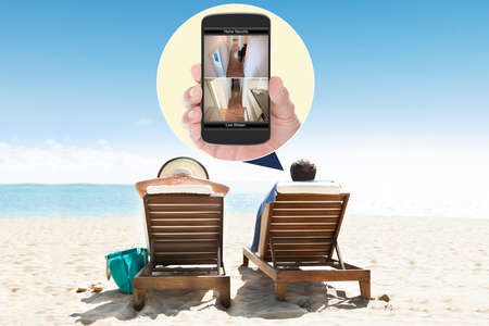 Man With Wife At Beach Looking At Security System On Mobile Phone