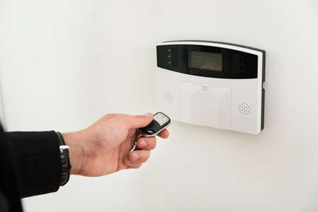 disarm: Close-up Of Businessperson Hands Operating Entrance Security System With Remote Control Stock Photo