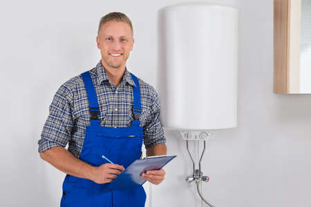 Young Happy Plumber In Overall Holding Clipboard And Pen
