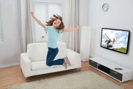 personas saltando: Linda Muchacha emocionada que salta en la sala de estar Foto de archivo