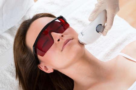 masaje facial: Mujer joven que recibe el tratamiento con l�ser depilaci�n En Cara En el Centro de Belleza