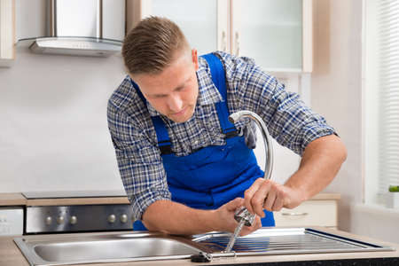 stainless steel sink: Young Repairman Installing Faucet Of Kitchen Sink In Kitchen Room