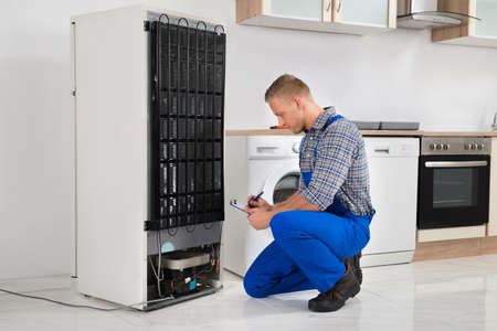refrigerator kitchen: Young Plumber Writing On Clipboard In Front Of Refrigerator Appliance In Kitchen Room
