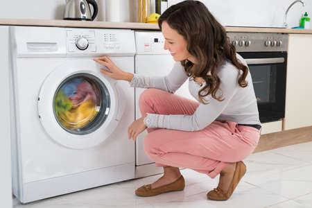 clothes washer: Mujer joven que mira la ropa giratorias dentro de la lavadora en la cocina en el hogar