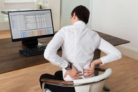 El hombre de negocios joven que se sienta en silla y que sufren de dolor de espalda en el escritorio