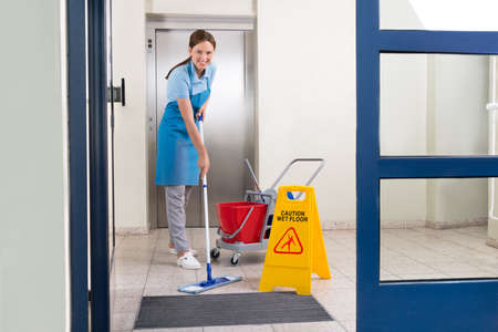 Happy Female Worker In Uniform Cleaning Floor With Mop