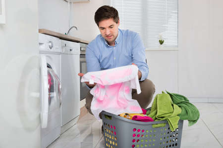 casual clothing: Man Near The Washing Machine With Laundry Basket Holding Stained Cloth In Kitchen Stock Photo