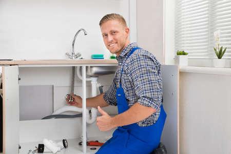 Happy Male Plumber Repairing Faucet In Kitchen Sink
