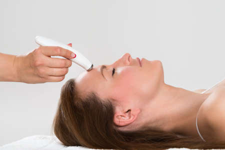 therapy equipment: Young Woman Receiving Microdermabrasion Therapy In Beauty Clinic