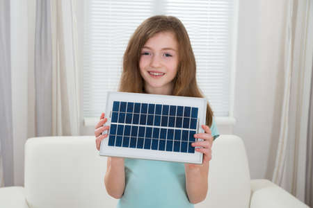 fuel and power generation: Happy Girl Holding Solar Panel In Living Room Stock Photo