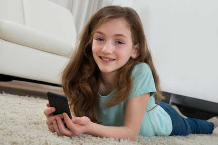 girl lying: Happy Girl With Mobile Phone Lying On Carpet In Living Room