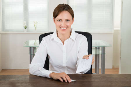 cheque: Happy Businesswoman Sitting At Desk Offering Cheque In Office Stock Photo