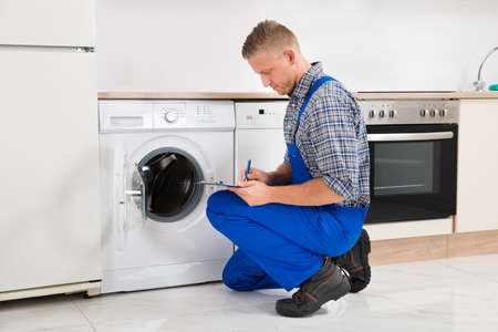 crouching: Repairman Crouching While Writing On Clipboard With Pen In Kitchen Stock Photo