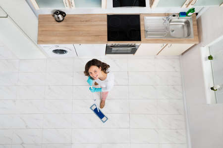 mopping: High Angle View Of Woman Mopping Floor In Kitchen Stock Photo