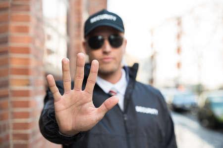 seguridad en el trabajo: Hombre Guardia de seguridad Haciendo muestra de la parada con las manos Foto de archivo