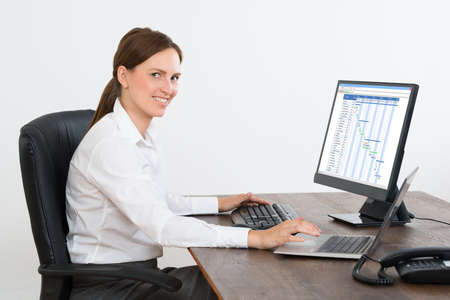 gantt: Young Businesswoman Working On Computer Showing Gantt Chart In Office