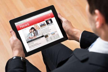 news online: Close-up Of Businessperson Reading News Online On Digital Tablet