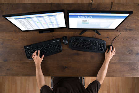 gantt: Man Working With Computers Showing Gantt Diagram And Signin App At Desk Stock Photo