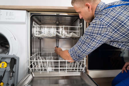 dishwasher: Young Man In Overall With Toolbox Repairing Dishwasher