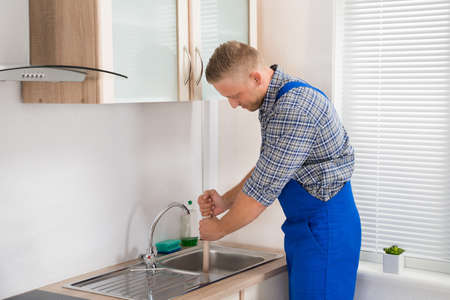 stainless steel sink: Male Plumber Using Plunger In Stainless Steel Sink In Kitchen Stock Photo