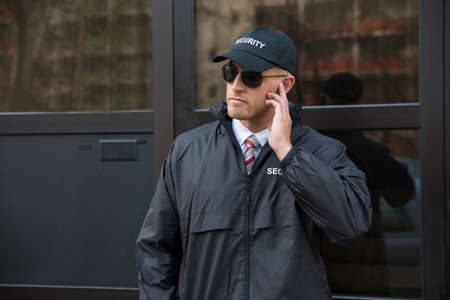 Junge Security Guard, der vor der Glastür Entrance Standard-Bild