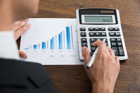 financial planner: Close-up Of Businessperson Analyzing Graph And Using Calculator At Desk
