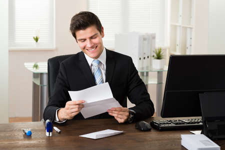 smiling businessman: Young Businessman Smiling While Reading Paper At Desk In Office