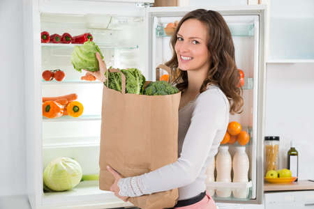 refrigerator with food: Happy Woman Holding Grocery Shopping Bag With Vegetables In Front Of Open Refrigerator