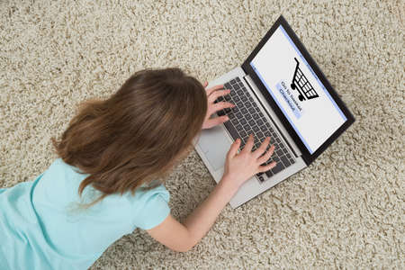 girl with laptop: High Angle View Of Girl Lying On Carpet Doing Online Shopping On Laptop Stock Photo