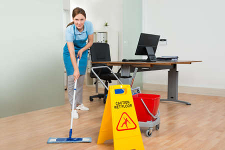 mujer limpiando: Feliz Janitor Mujer con la limpieza de equipos de limpieza Suelo de madera en oficina