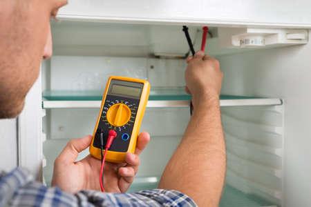 gospodarstwo domowe: Młody Mężczyzna Technik Sprawdzanie lodówka z multimetr cyfrowy Zdjęcie Seryjne