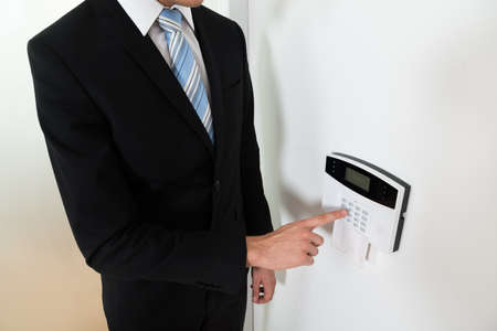 Close-up Of Young Businessman Setting Home Security Alarm System
