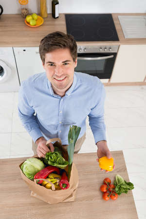 high angle: High Angle View Of Man Removing Vegetables From Grocery Bag In Kitchen Stock Photo