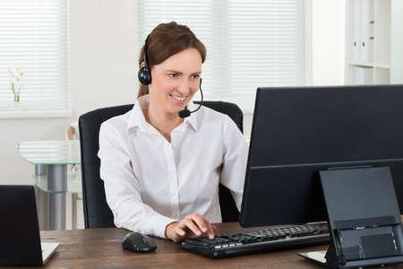 사무실에서 컴퓨터에 근무하는 헤드셋 여성 고객 서비스 담당자