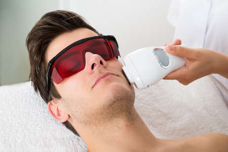 depilation: Young Man Receiving Laser Hair Removal Treatment At Beauty Center Stock Photo