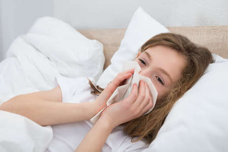 cold virus: Sick Girl On Bed Sneezing In Handkerchief In Bedroom