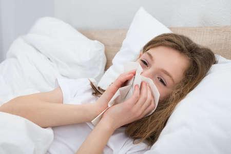 cold virus: Sick Girl On Bed Sneezing In Handkerchief In Bedroom