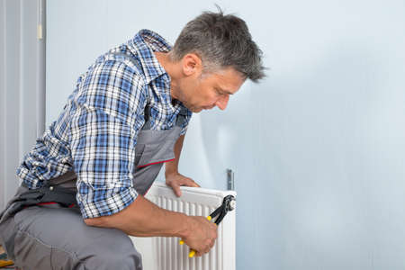 Portrait Of Male Plumber Fixing Radiator With Wrench