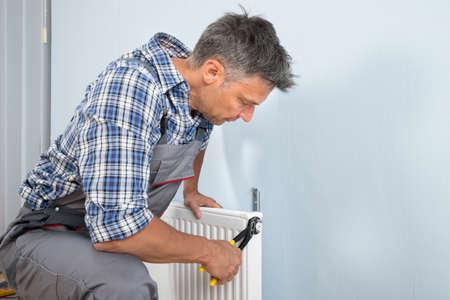 Ritratto del maschio Idraulico di fissaggio del radiatore Con La Chiave