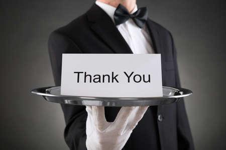 Крупным планом официанта удерживающая пластина с текстом Спасибо на бумаге