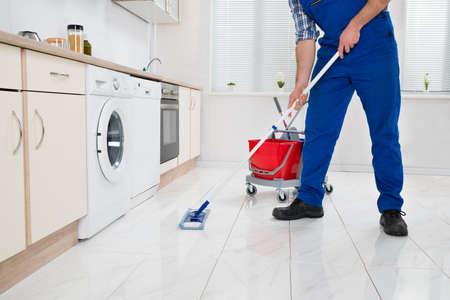 orden y limpieza: Close-up de los trabajadores de limpieza del piso con la fregona en cocina Sala Foto de archivo