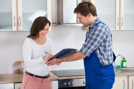 customer records: Happy Woman Writing On Clipboard In Front Of Young Plumber Standing In Kitchen Stock Photo