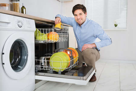 apartment cleaning: Young Happy Man Arranging Dishes In Dishwasher In Modern Kitchen Stock Photo