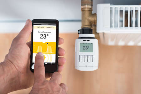 wireless: Close-up Of Persons Hand Adjusting Temperature Of Thermostat Using Cellphone. Photographer owns copyright for images on screen